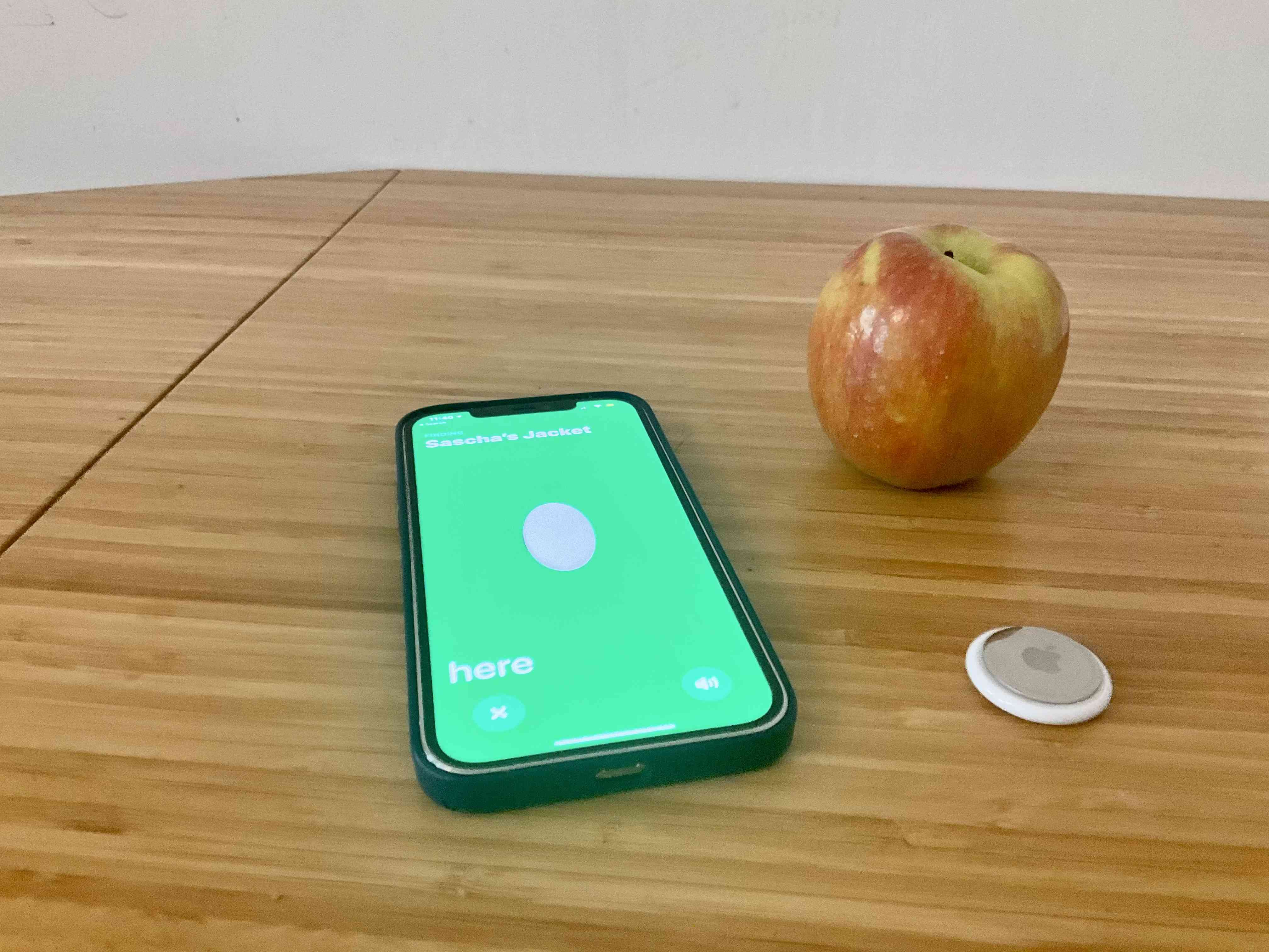 Apple AirTag paired with an iPhone and next to an Apple for size comparison