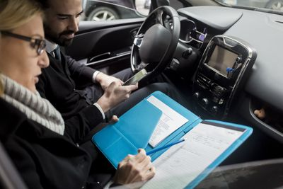 Two people in a car looking at files