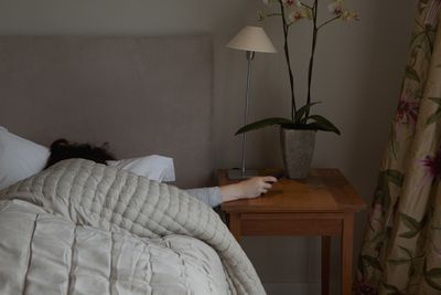 A person under a quilt cover reaching out to their bedside smartphone