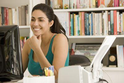 Woman sitting at desk, looking at computer.