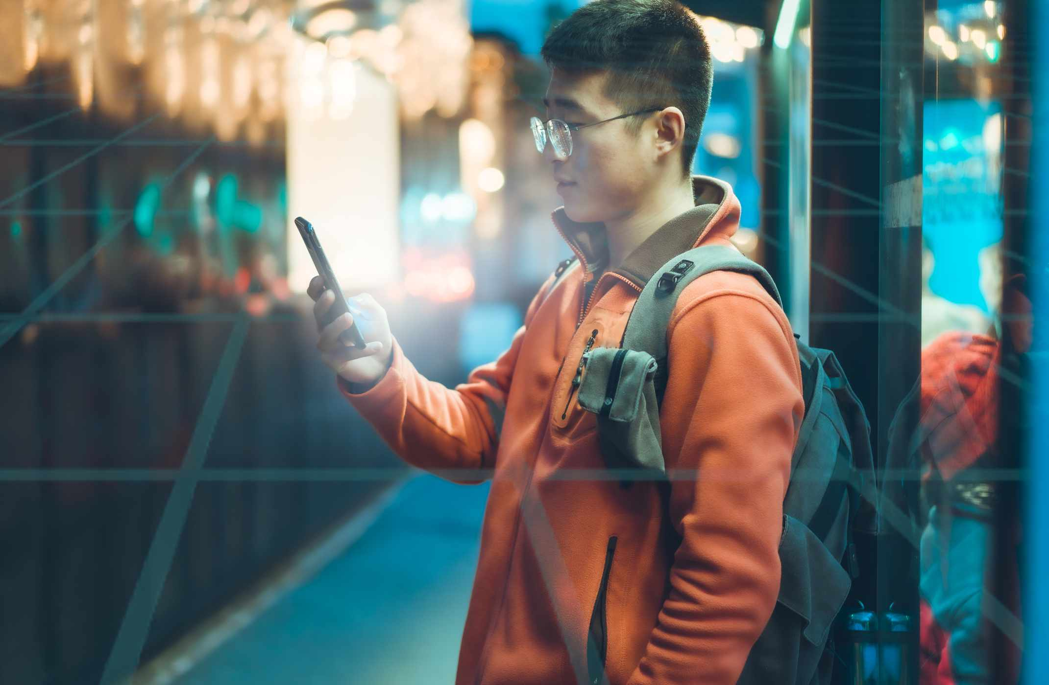 Someone using a smartphone outdoors in a city setting with a grid overlaying the image.