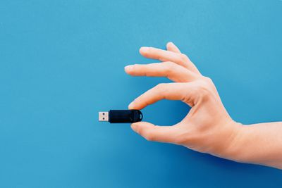 Hand holding a USb flash drive on a blue background