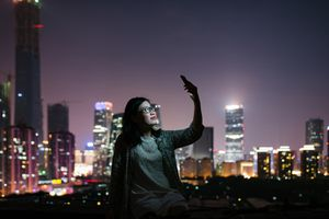 A stock photo of a woman taking selfies with her smartphone on a rooftop at night.