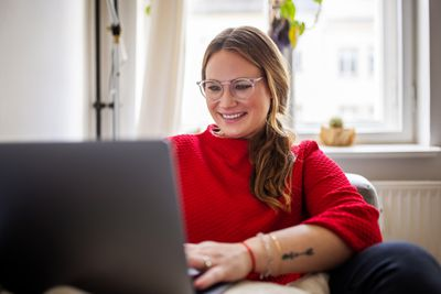 A woman smiling at her laptop while sitting down