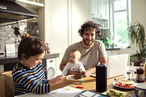 A family sitting at a kitchen table, with a smart speaker in the middle of the table.