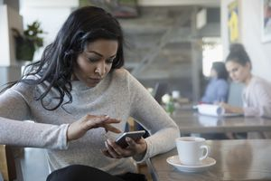 Woman in cafe using her iPhone