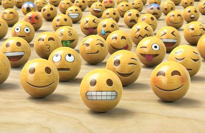 Many wooden emoticon or Emoji face balls.