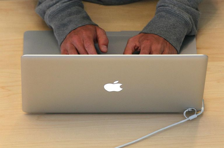 A customer types on a MacBook laptop at an Apple Store.