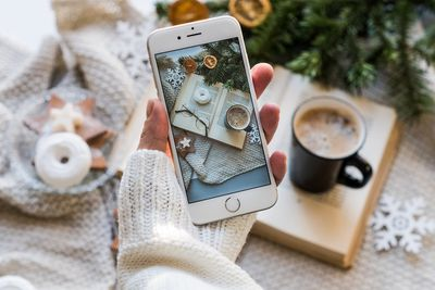 Person's hand holds white iPhone over coffee and table scene they just took a photo of.