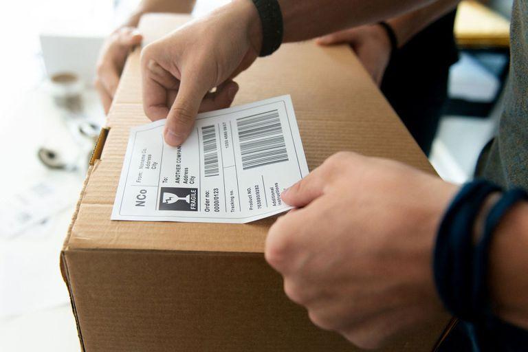 A man sticking his own barcode sticker onto a box.