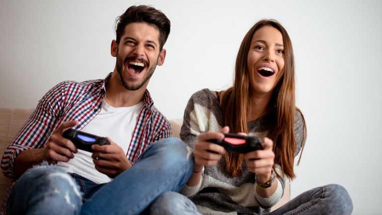 Man and woman playing Sony's Playstation 4