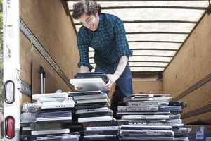 Someone moving stacks of recycled laptop computers.