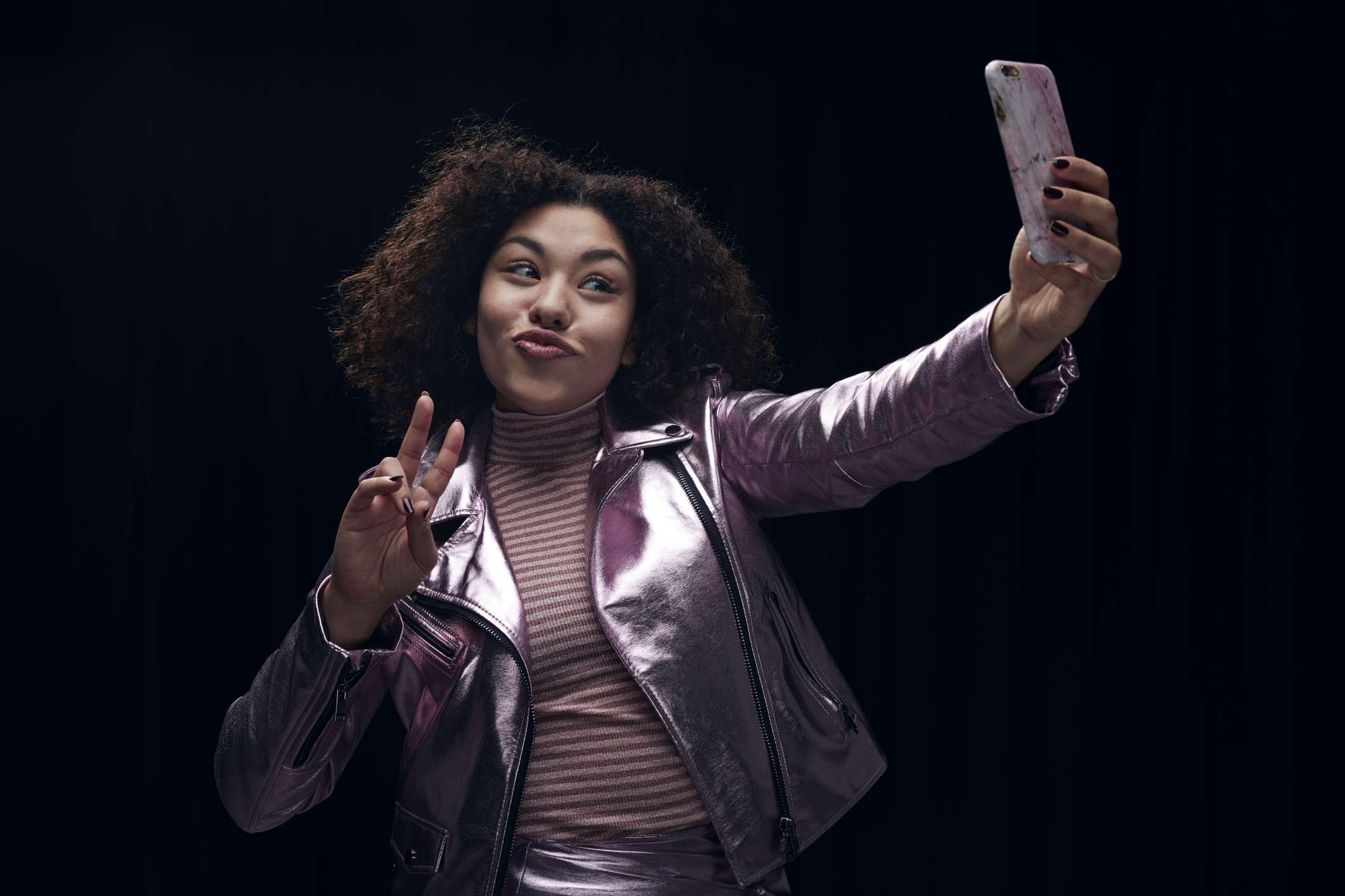 Woman doing the peace sign taking a selfie.