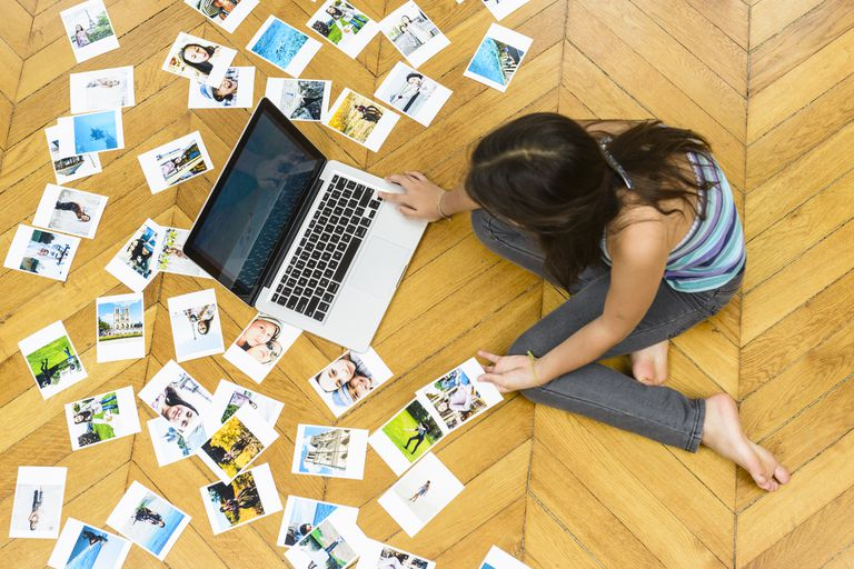 Young girl is sorting and printing her vacation pictures