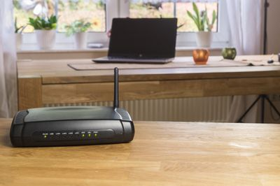 A wireless modem with a laptop in the background.