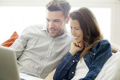 Couple relaxing at home looking at laptop computer with Facebook See First friends