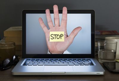 A hand with a stickynote that says STOP coming out of a laptop display