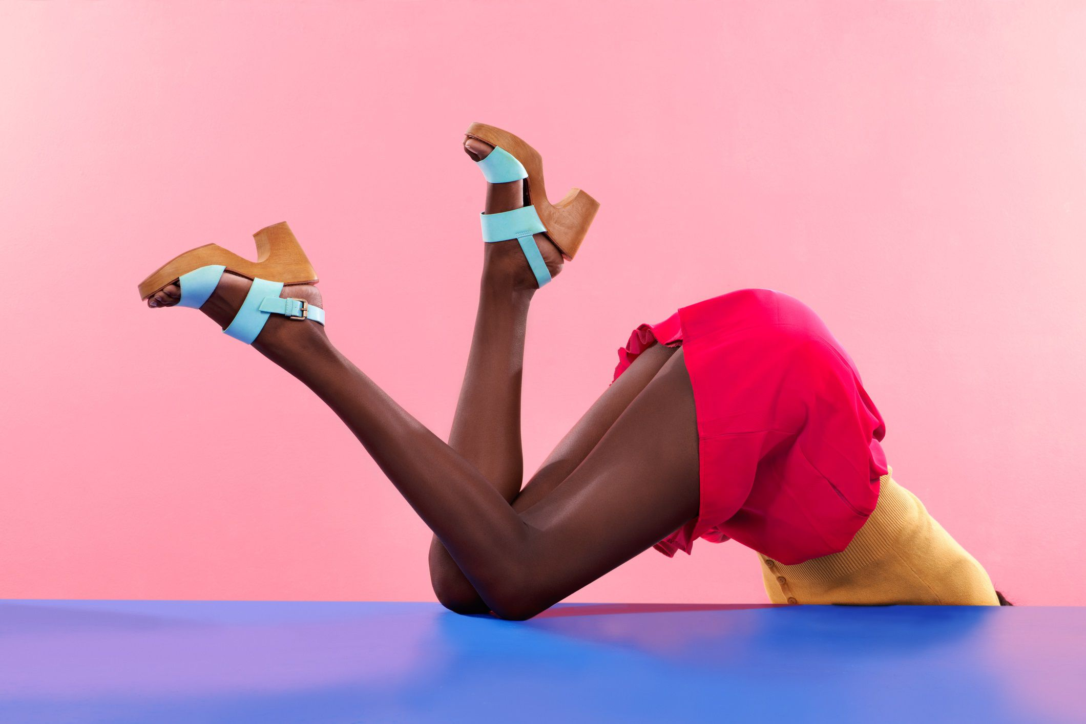 headless girl with heels, upside down, hanging off edge of table