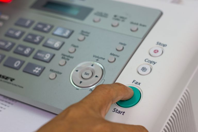 A close-up of someone using a fax machine in an office