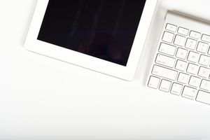 Tablet on White Office Desk with Computer Keyboard and Copy Space