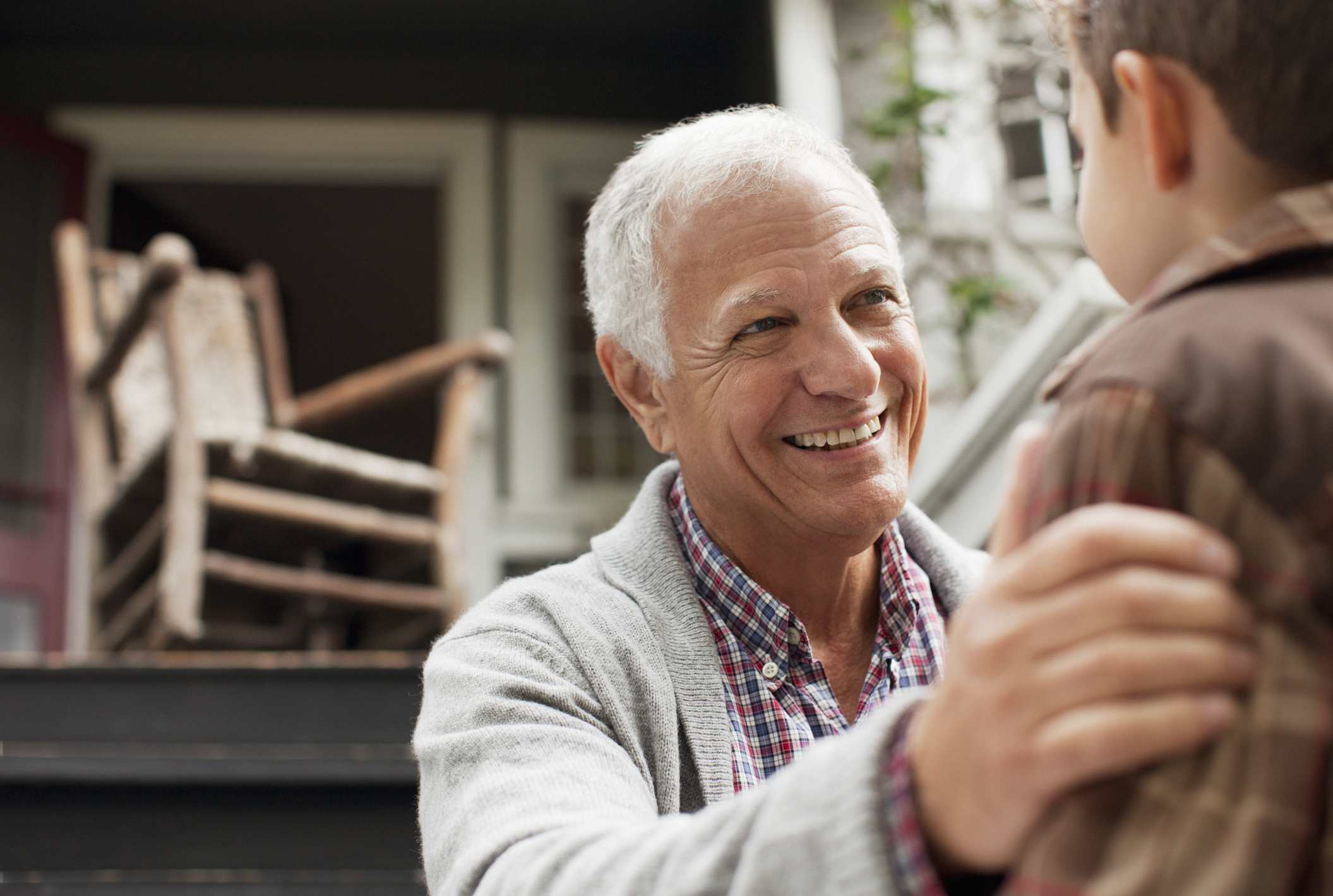 Older man embracing young boy's shoulder smiling