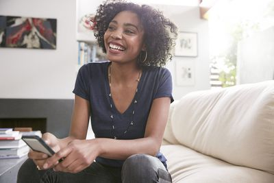 Smiling African American woman with cell phone on living room sofa