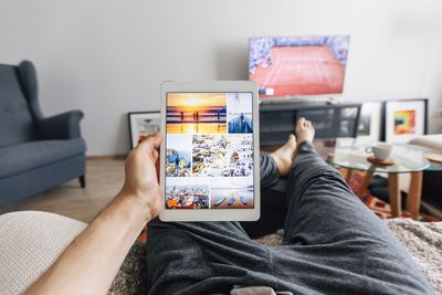 Man stretched out on the couch looking at an iPad