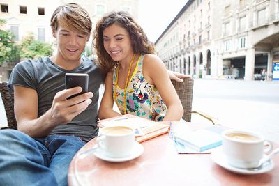 Tourist couple using smartphone in coffee shop.