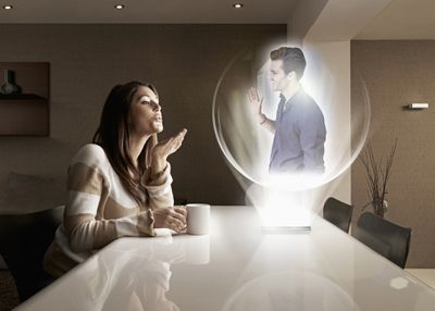A couple having a conversation, one person in holographic form.