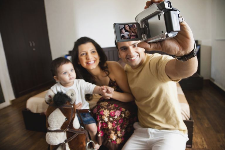 A man holding a camcorder towards himself and his family.