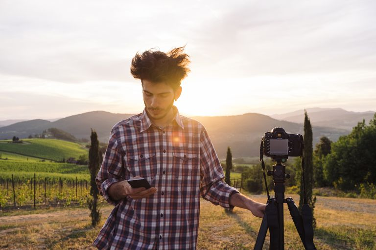A man uses the Canon Camera Connect app to take a photo remotely.