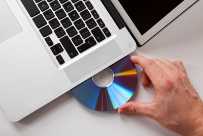Photo of a hand inserting a disc into a laptop computer
