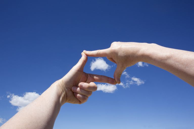 Hands framing a cloud against a blue sky.