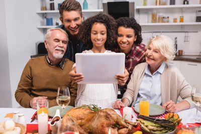 A family gathers for Thanksgiving and uses an iPad to connect with distant relatives