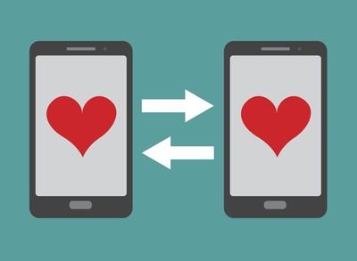Two smartphones with hearts on both screens.