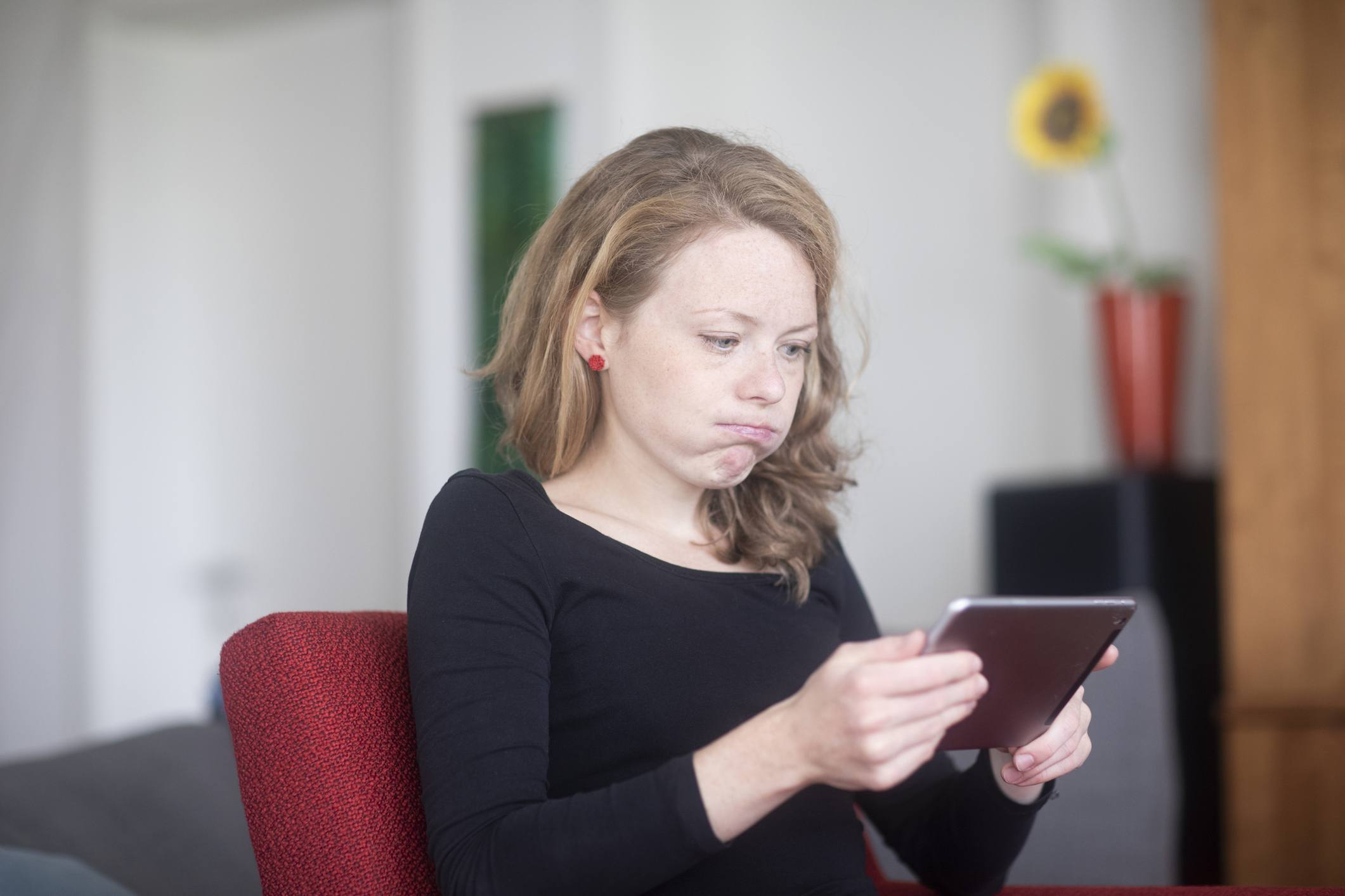 Woman using a digital tablet blowing her cheeks