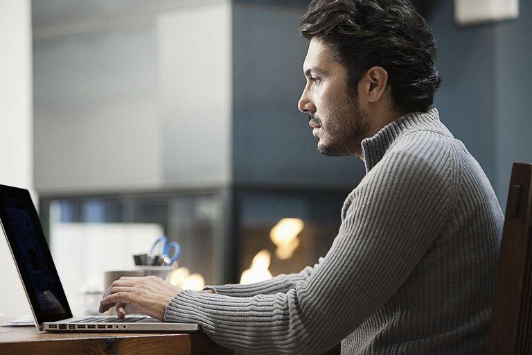 Hispanic man typing on laptop