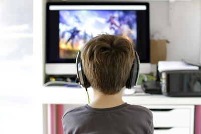 A child sitting with headphones on staring at a screen, playing a game