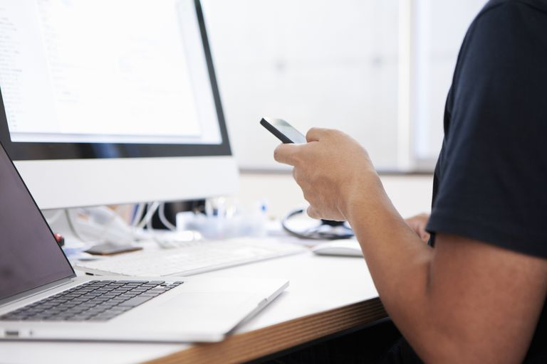 Man using iPhone in front of mac laptop and desktop computer