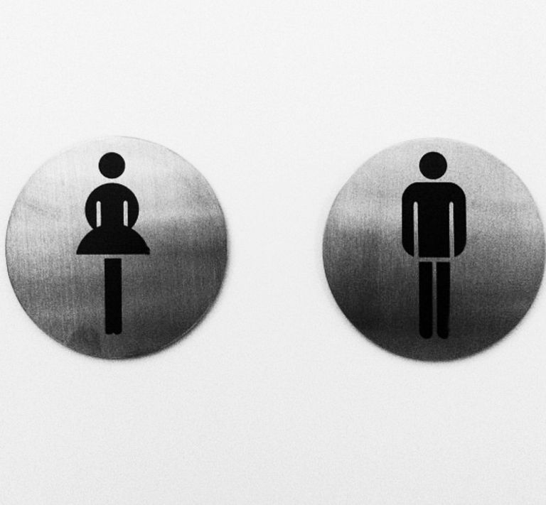 Close-Up Of Male And Female Toilet Signs On Wall