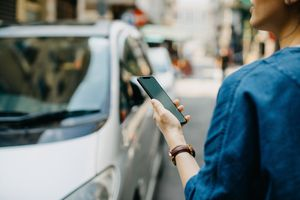 Woman holding an iPhone using Uber to catch a ride