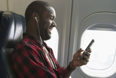 Man watching video on his phone on an airplane