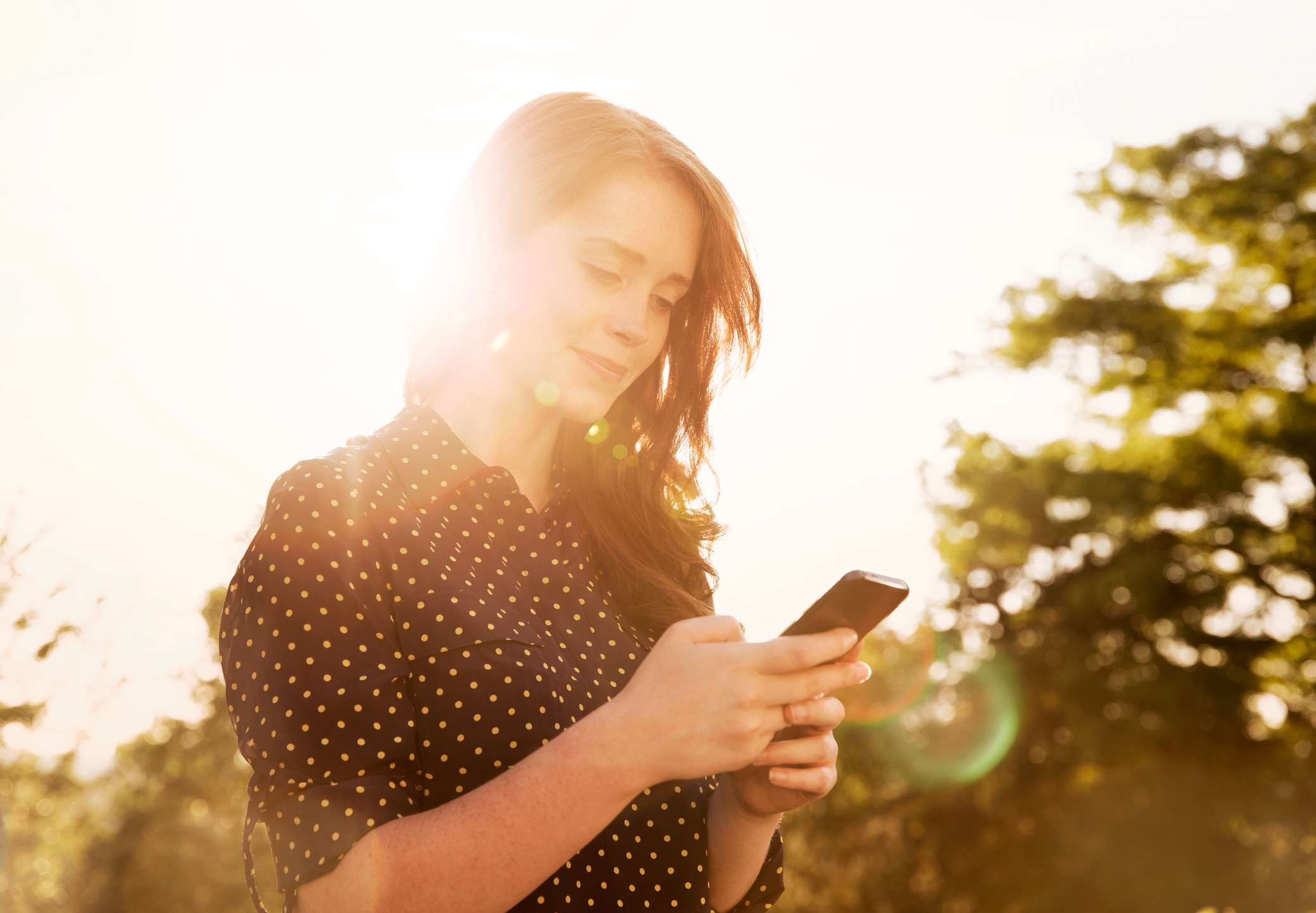 Someone using a smart phone with a bright sun behind them.