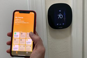Photo of iPhone with Home app showing 9 devices, and ecobee thermostat in the background