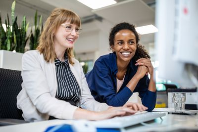 Female colleagues smiling while looking at computer