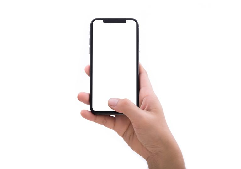 Close up of a hand holding a phone with a blank white screen.