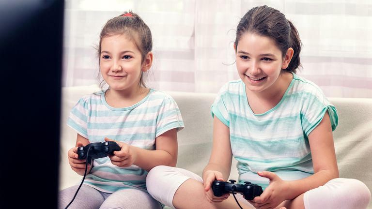 Two young girls playing fun video games on their PlayStation console.