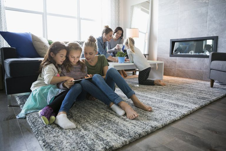Girls on a playdate using mobile devices on home network.