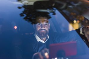 Commuter using a navigation device in car at night