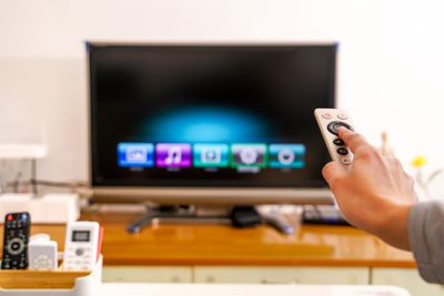 A hand pointing a remote control at a TV
